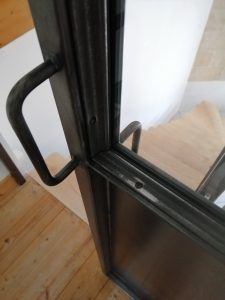 Porte vitrée coulissante en acier ciré